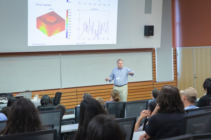 A man stands in front a projected image delivering a talk to a crowded lecture hall.