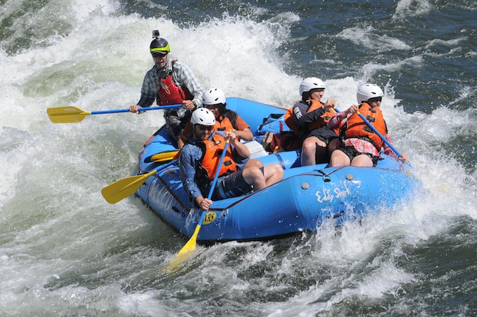 Five people holding oars and wearing orange life vests rafting down a river in a blue raft.