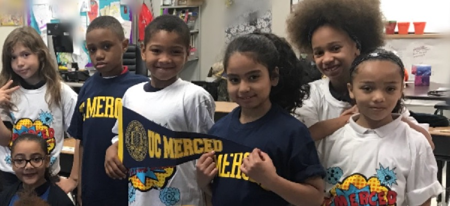 Kids wearing donated UC Merced shirts from SNS